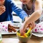 Kinder essen Pommes und Rohkost